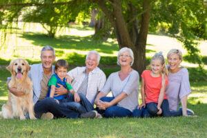 Mehrgenerationen Familie - Eltern, Großeltern, Kinder, Enkel, Hund auf Wiese