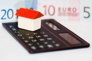 Haus mit Taschenrechner und Geldschein